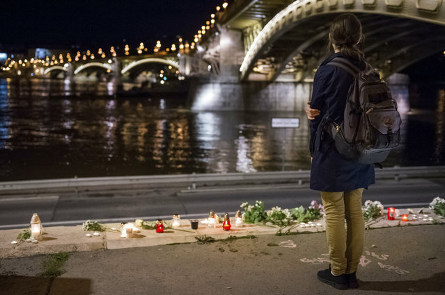 A woman stands by flowers and candles placed on the riverbank to pay tribute to the victims of the capsized boat at Margaret Bridge, in Budapest, Hungary, Thursday, May 30, 2019. Rescue crews in Hungary's capital are preparing to raise a sightseeing boat from the bottom of the Danube River Thursday as search teams scoured the waters for 21 people missing after the vessel, packed with South Korean tourists, collided with a larger cruise ship and sank. Seven people are confirmed dead and seven were rescued, all of them South Koreans. (Photo by Zoltan Mathe/MTI via AP Photo)