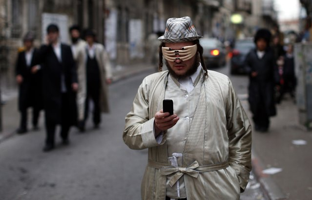 An Ultra-Orthodox Jewish man wears a mask as he celebrates the Purim holiday in the ultra-orthodox Mea Shearim neighborhood in Jerusalem on March 17, 2014. The carnival-like Purim holiday is celebrated with parades and costume parties and drinking wine to commemorate the deliverance of the Jewish people from a plot to exterminate them in the ancient Persian empire 2,500 years ago, as recorded in the Biblical Book of Esther. (Photo by Thomas Coex/AFP Photo)