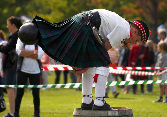 A competitor wearing a kilt and standing on a barrel throws a bowling ball between her legs during the 'Brigaball' contest at the annual Bundanoon Highland Gathering, showcasing traditional Scottish events, held in the town of Bundanoon, located southwest of Sydney, April 9, 2016. (Photo by David Gray/Reuters)