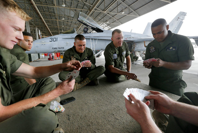U.S. Marines play spades during a break at the 309th Aerospace Maintenance and Regeneration Group boneyard in Tucson, Ariz. on Thursday, May 21, 2015. The Marines are repairing F-A-18's to return to service at the 309th facility. (Photo by Matt York/AP Photo)