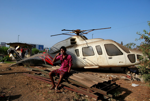 A migrant labourer brushes his teeth in front of a scrapped helicopter model in Mumbai, India, April 13, 2016. (Photo by Danish Siddiqui/Reuters)