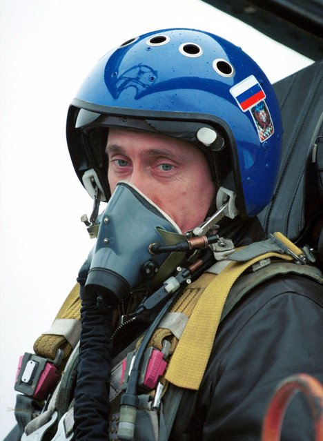 In this March 20, 2000 file photo, President Vladimir Putin, wearing a blue helmet and an oxygen mask, sits in Su-27 fighter jet after his flight into the war zone in Chechnya, in Grozny, Russia. (Photo by AP Photo/ITAR-TASS/Presidential Press Service)