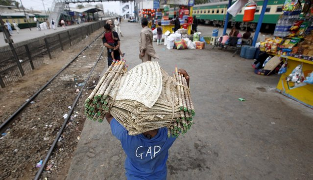 A boy carries a hand fans on his head while selling them along Cantonment Railways Station in Karachi, Pakistan, May 25, 2015. (Photo by Akhtar Soomro/Reuters)