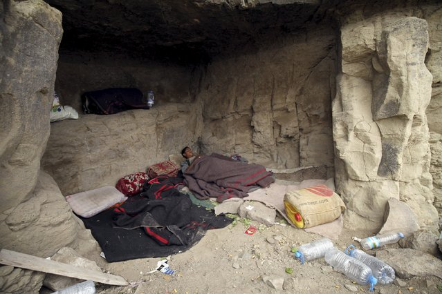 A youth sleeps in a cave after his home was destroyed during an air strike carried out by the Saudi-led coalition in Faj Attan village, Sanaa, Yemen May 7, 2015. (Photo by Mohamed al-Sayaghi/Reuters)