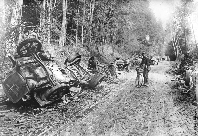 1914: A lone soldier with a bicycle stands amid the remains of a German motor convoy which lines a country lane after an attack by French field guns in the battle of the Aisne in France