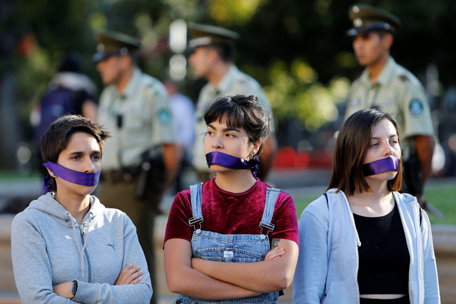Women cover their mouths as they attend a peaceful demonstration in front of the government house as part of International Women's Day, in Santiago, Chile March 8, 2017. (Photo by Carlos Vera/Reuters)
