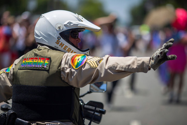 A Los Angeles County Sheriffs deputy wear rainbow colors during the annual LA Pride Parade in West Hollywood, California, on June 9, 2019. LA Pride began on June 28, 1970, exactly one year after the historic Stonewall Rebellion in New York City, 50 years ago. (Photo by David McNew/AFP Photo)