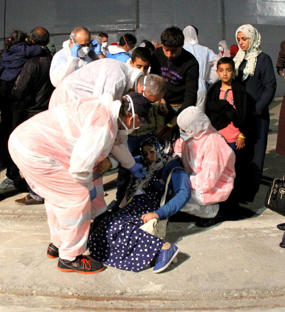 A migrant woman faints after disembarking from the German Navy ship Schleswig Holstein  at the Reggio Calabria harbor, Italy, Tuesday, June 16, 2015. European Union nations failed to bridge differences Tuesday over an emergency plan to share the burden of the thousands of refugees crossing the Mediterranean, while on the French-Italian border, police in riot gear forcibly removed dozens of migrants. (AP Photo/Adriana Sapone)
