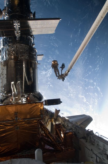 Mission Specialist John Grunsfeld is positioned on a foot restraint on the end of Atlantis' remote manipulator system and Andrew Feustel (top center), mission specialist, participate in the mission's fifth and final spacewalk, May 20, 2009. (Photo by NASA)