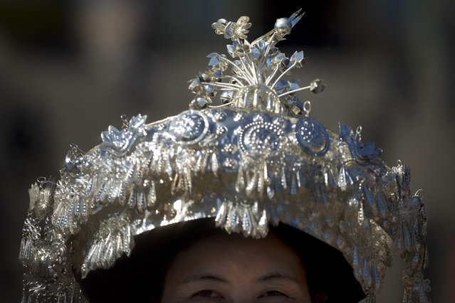 In this Sunday, March 12, 2017 photo, an ethnic minority delegate wears a hat topped with a silver bird as she leaves a plenary session of China's National People's Congress (NPC) at the Great Hall of the People in Beijing. (Photo by Mark Schiefelbein/AP Photo)