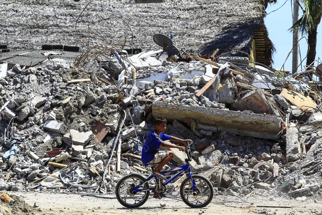 A boy rides a bicycle in front of debris of a destroyed building in Canoa, Ecuador, 25 April 2016. The death toll from the magnitude 7.8 earthquake that hit Ecuador's north coast on 16 April has risen to 655, according to the National Risk Management Secretariat (SNGR). (Photo by Jose Jacome/EPA)