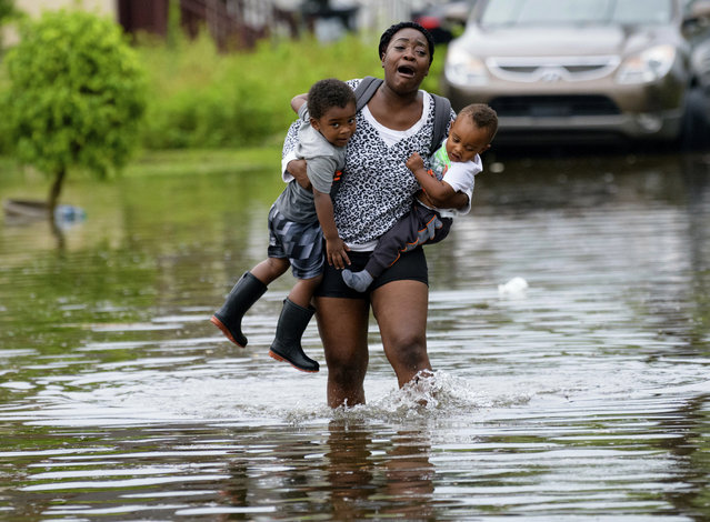 Terrian Jones reacts as she feels something moving in the water at her feet as she carries Drew and Chance Furlough to their mother on Belfast Street in New Orleans during flooding from a storm in the Gulf Mexico that dumped lots of rain, July 10, 2019. (Photo by Matthew Hinton/AP Photo)