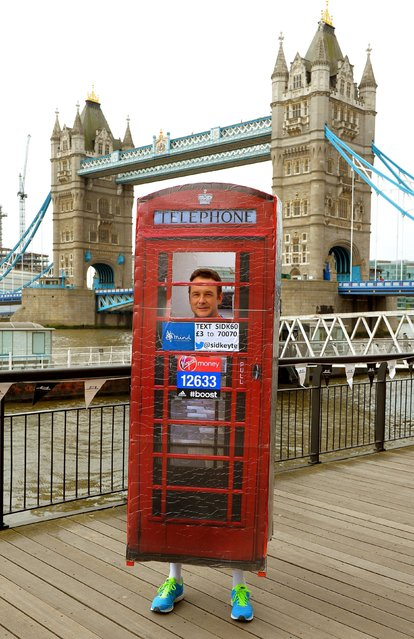 Sid Keyte aged 43 from Salisbury in his home-made telephone box in which he will run for charity during the photocall at Tower Bridge, London, on April 11, 2014. (Photo by John Stillwell/PA Wire)