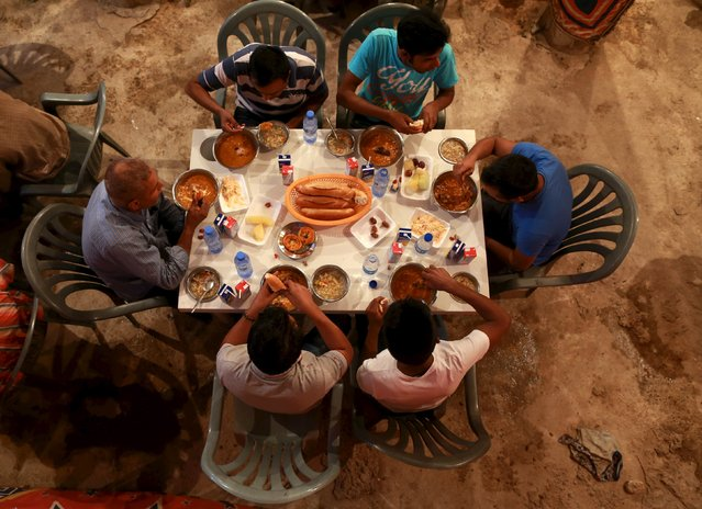 People eat their Iftar (breaking of fast) meal at a table offering free food set up by a charity during the holy fasting month of Ramadan in Benghazi, Libya June 27, 2015. (Photo by Esam Omran Al-Fetori/Reuters)