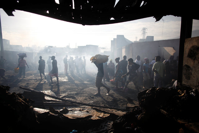 Haitians walk in the remains of a fire in a market in Port-au-Prince, Haiti, March 20, 2017. (Photo by Andres Martinez Casares/Reuters)