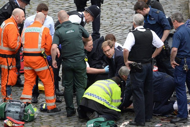 London : Conservative Member of Parliament Tobias Ellwood, centre, helps emergency services attend to an injured person outside the Houses of Parliament, London, Wednesday, March 22, 2017. (Photo by AP Photo/PTI)