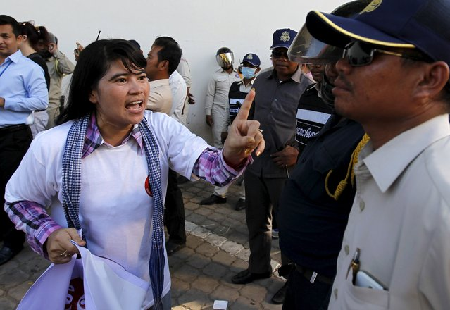 A woman reacts as Cambodian police officers block her during a protester's march along a street in Phnom Penh June 30, 2015. Hundreds of land rights activists and non-governmental organization (NGO) workers rallied on Tuesday against two controversial draft laws, the laws on Association and Non-Governmental Organizations and Trade Union Law. (Photo by Samrang Pring/Reuters)