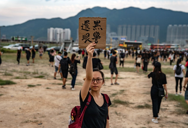"A protester holds up a placard which roughly translates as ""policeman give the eye back"" outside the Hong Kong International Airport as protesters retreat during a demonstration on August 12, 2019 in Hong Kong, China. Pro-democracy protesters have continued rallies on the streets of Hong Kong against a controversial extradition bill since 9 June as the city plunged into crisis after waves of demonstrations and several violent clashes. Hong Kong's Chief Executive Carrie Lam apologized for introducing the bill and declared it ""dead"", however protesters have continued to draw large crowds with demands for Lam's resignation and completely withdraw the bill. (Photo by Anthony Kwan/Getty Images)"