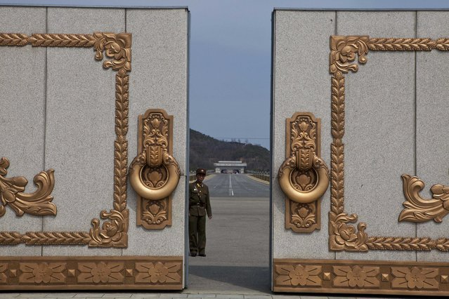 A North Korean soldier guarding the entrance to Pyongyang's Kumsusan mausoleum, where the bodies of the late leaders Kim Il Sung and Kim Jong Il lie embalmed, looks back through the doors of the main gate Monday, April 15, 2013. (Photo by David Guttenfelder/AP Photo)