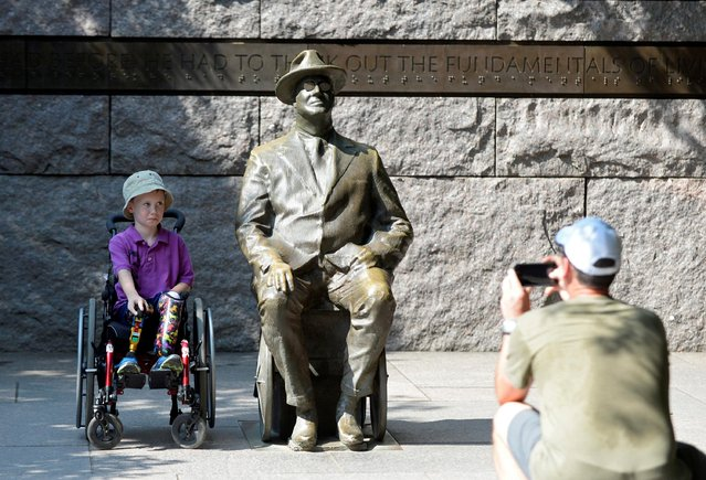Ulysses Watko, 7, visiting from Portland, OR, sits next to a sculpture of Franklin Delano Roosevelt in his wheelchair while his dad Brian Watko takes a picture at the Franklin Delano Roosevelt Memorial in Washington, U.S., August 7, 2019. (Photo by Mary F. Calvert/Reuters)