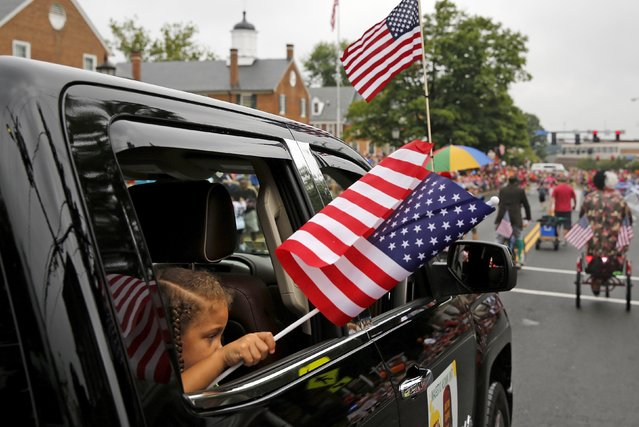 A little girl waves a U.S. flag as she takes part in the Independence Day Parade in Fairfax, Virginia July 4, 2015. (Photo by Jonathan Ernst/Reuters)