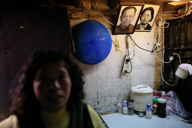 A woman surnamed Li stands inside the house she shares with her husband as pictures of her mother-in-law and father-in-law are seen on the wall, in the Guangfuli neighbourhood, in Shanghai, China, April 8, 2016. (Photo by Aly Song/Reuters)