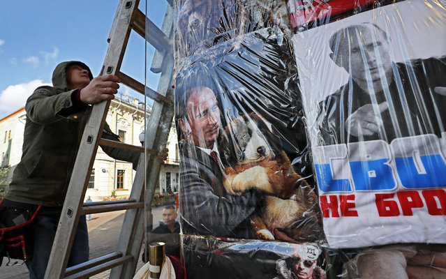 A man climbs a ladder near the storefront with t-shirts with portraits of Russian President Vladimir Putin in Moscow, Russia, 16 September 2019. (Photo by Yuri Kochetkov/EPA/EFE)