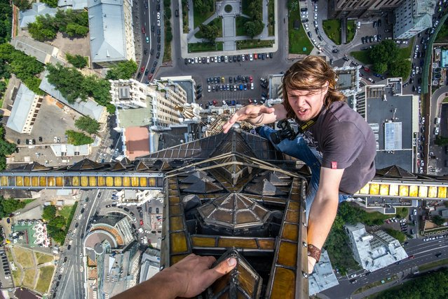 Yaroslav Segeda at the top of a high rise building in Kudrinskaya Square, Moscow, Russia. (Photo by Yaroslav Segeda/Caters News)