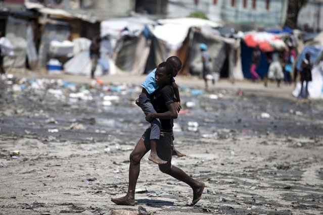 A youth carries a younger one away from protesters and toward police to ask for help, after he was overcome by tear gas fired by police outside Parliament where lawmakers are debating whether or not to start impeachment proceedings for Haitian President Jovenel Moise in Port-au-Prince, Haiti, Wednesday, August 21, 2019. Ongoing protests have been demanding that Moise resign over corruption allegations. (Photo by Dieu Nalio Chery/AP Photo)