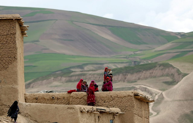 In this Sunday, May 4, 2014 photo, Survivors sit with their possessions near the site of Friday's landslide that buried Abi-Barik village in Badakhshan province, northeastern Afghanistan. Stranded and with no homes, many of the families have struggled to get aid. Some have gone to nearby villages to stay with relatives or friends, while others have slept in tents provided by aid groups. The unlucky ones have slept outside. (Photo by Massoud Hossaini/AP Photo)