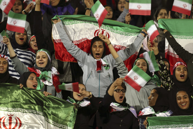 "In this October 16, 2018 file photo, Iranian women cheer as they wave their country's flag after authorities in a rare move allowed a select group of women into Azadi stadium to watch a friendly soccer match between Iran and Bolivia, in Tehran, Iran. Sahar Khodayari, an Iranian female soccer fan died after setting herself on fire outside a court after learning she may have to serve a six-month sentence for trying to enter a soccer stadium where women are banned, a semi-official news agency reported Tuesday, Sept. 10, 2019. The 30-year-old was known as the ""Blue Girl"" on social media for the colors of her favorite Iranian soccer team, Esteghlal. (Photo by Vahid Salemi/AP Photo/File)"