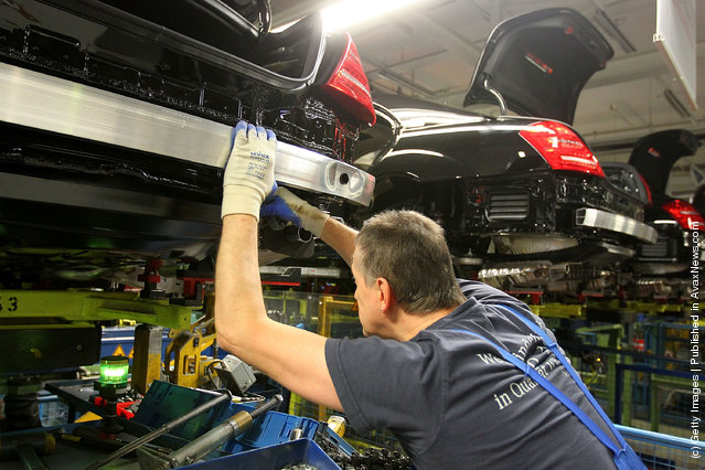 Employees mounts to a Daimler AG Mercedes-Benz S-Class vehicle on the production line