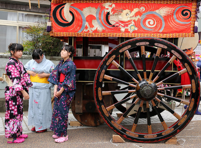 Japanese women dressed Kmno costumes stand beside a huge wheel of doll cart during the Mikuini annual festival on May 20, 2014 in Sakai, Japan. The annual festival takes place from May 19-21 and is attended by thousands of visitors. During the festival people dressed in traditional Japanese costumes pull carts carrying 6 meter high dolls of Japanese historical figures through the narrow streets. The origins of the festival are unclear but its history can be traced back more than 250 years. (Photo by Buddhika Weerasinghe/Getty Images)