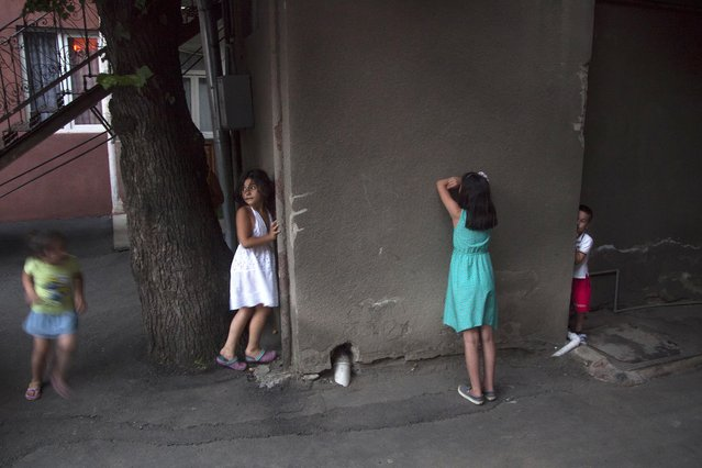 In this Saturday, July 11, 2015 photo, children play hide and seek in Tbilisi, Georgia. (Photo by Tinatin Kiguradze/AP Photo)