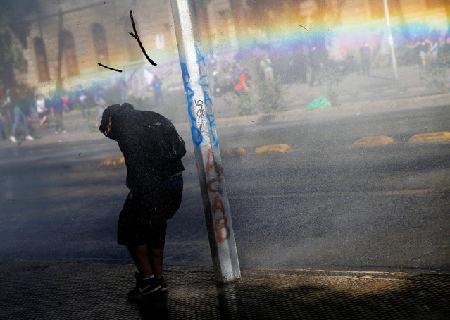 A demonstrator takes cover from tear gas and a water cannon during an anti-government protest in Santiago, Chile on October 30, 2019. (Photo by Edgard Garrido/Reuters)