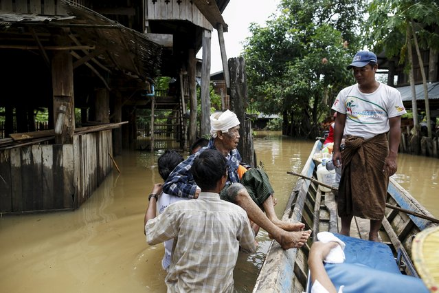 Local people carry old man in a flooded village in Kawlin township, Sagaing division, Myanmar, July 21, 2015. (Photo by Soe Zeya Tun/Reuters)