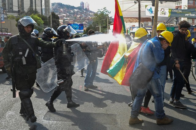 Riot police fire tear gas to disperse people taking part in a blockade to protest against the results of the October 20 elections in La Paz, on November 4, 2019. Bolivia's government accused its rivals Sunday of plotting deadly violence against it after an opposition figure vowed to oust leftist President Evo Morales and called for the military's support. Deadly unrest has gripped the South American country since Morales was named winner of the October 20 election for a fourth term. (Photo by Jorge Bernal/AFP Photo)