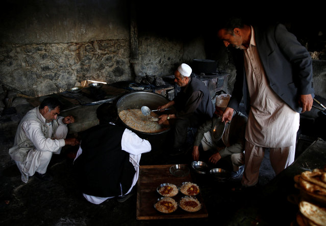A cook (C) prepares lunch to be distributed to workers at the Jabal Saraj cement factory in Jabal Saraj, north of Kabul, Afghanistan May 8, 2016. (Photo by Ahmad Masood/Reuters)