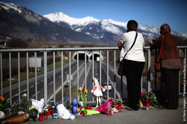Members of the public lay flowers on a bridge near to the road tunnel where the 22 Belgian school children, four teachers and two drivers died in a coach crash, on March 15, 2012 in Sierre, Valais, Switzerland