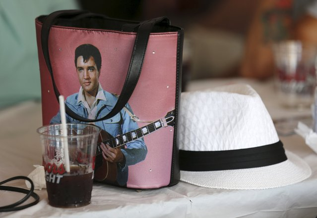 A fan's purse featuring the image of Elvis Presley lies on a bar table during the four-day Collingwood Elvis Festival in Collingwood, Ontario July 25, 2015. (Photo by Chris Helgren/Reuters)
