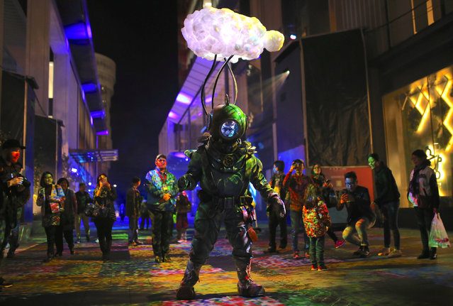 """A man wearing an illuminated atmospheric diving suit as part of an installation titled """"What Lies Beneath"""" looks at members of the public during the Vivid Sydney festival of light and sound in Sydney, Australia, May 26, 2017. (Photo by Steven Saphore/Reuters)"""