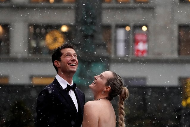 People pose for photos in the snow in the Manhattan borough of New York City, New York, U.S., December 2, 2019. (Photo by Carlo Allegri/Reuters)