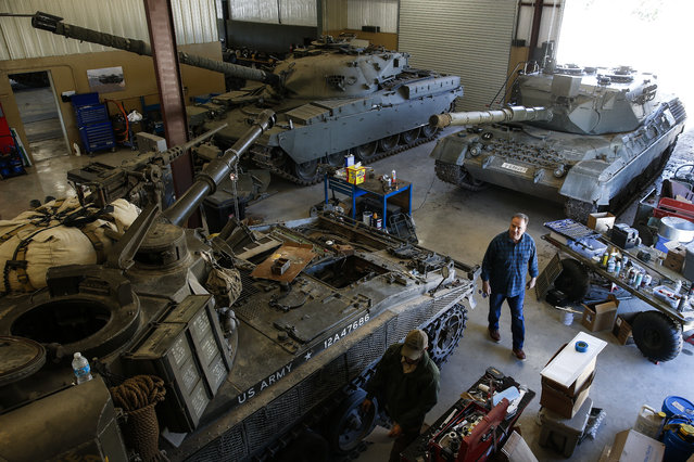 In this May 24, 2017, photo, Scott Jones gets a tour of the historic tanks in the DriveTanks.com garage at Ox Ranch  in Uvalde, Texas. (Photo by Michael Ciaglo/Houston Chronicle via AP Photo)