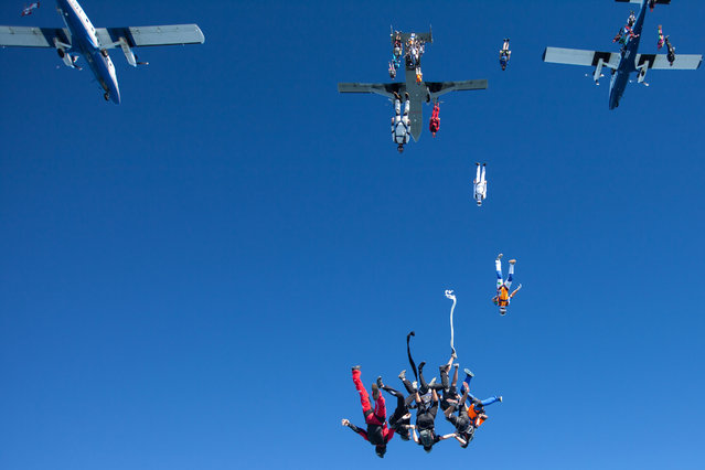 In this photo provided by Jason Peters, members of an international team of skydivers exit jump planes flying head-down on their way to building their world record skydiving formation Friday, July 31, 2014, over Ottawa, Ill. (Photo by Jason Peters via AP Photo)