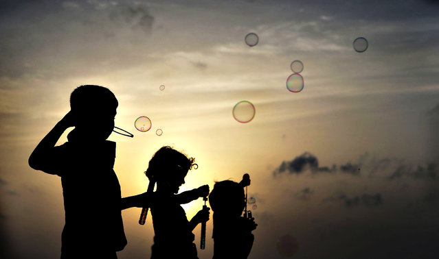 Sri Lankan children playing with soap bubbles are silhouetted against the setting Sun in Colombo, Sri Lanka, Tuesday, June 24, 2014. (Photo by Eranga Jayawardena/AP Photo)