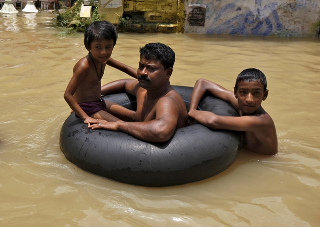 Flood-affected people use a tyre tube as they move to safer grounds through the flood waters at West Midnapore district in West Bengal, India, August 4, 2015. At least 75 people have died and tens of thousands have had to take refuge in state-run relief camps after heavy rains caused floods and landslides in eastern India, government officials and aid groups said on Monday. (Photo by Rupak De Chowdhuri/Reuters)