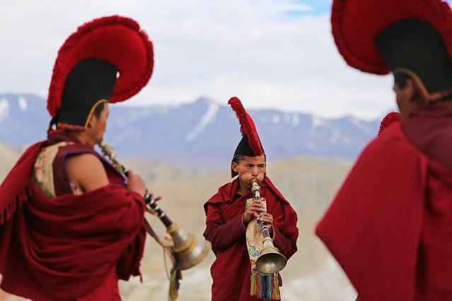 Monks play music and perform Buddhist ceremonies outside of the city gates during the Tenchi Festival on May 27, 2014 in Lo Manthang, Nepal. The Tenchi Festival takes place annually in Lo Manthang, the capital of Upper Mustang and the former Tibetan Kingdom of Lo. Each spring, monks perform ceremonies, rites, and dances during the Tenchi Festival to dispel evils and demons from the former kingdom. (Photo by Taylor Weidman/Getty Images)