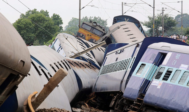 Damaged train coaches at the site of a train accident, 180 kilometers from Bhopal near Harda district of Mahdya Pradesh, India, 05 August 2015. At least 25 people died when two passenger trains derailed in central India after heavy monsoon rains flooded railway tracks, officials said. Ten coaches from the trains toppled while approaching a small bridge just before midnight. (Photo by Sanjeev Gupta/EPA)