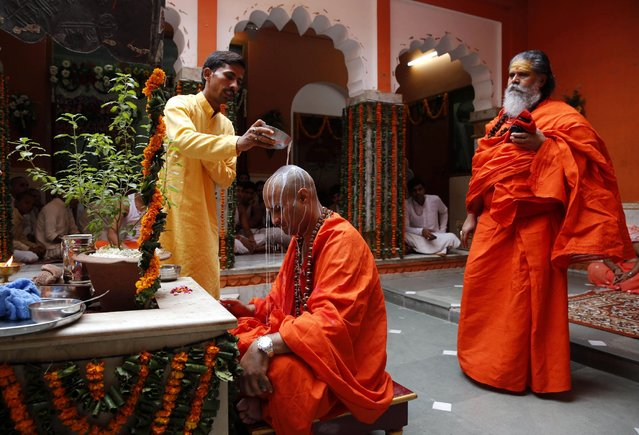 A devotee pours milk on the head of his Guru as a mark of respect on the occasion of Guru Purnima, or full moon day dedicated to the Guru, in Allahabad, India, Friday, July 31, 2015. The festival is celebrated as a day to worship and express gratitude to teachers. (Photo by Rajesh Kumar Singh/AP Photo)