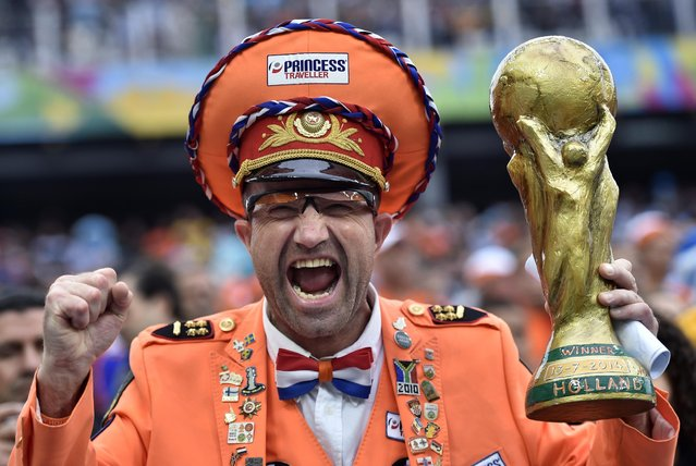 A Dutch supporter reacts as he holds a replica of the World Cup before the World Cup semifinal soccer match between the Netherlands and Argentina at the Itaquerao Stadium in Sao Paulo Brazil, Wednesday, July 9, 2014. (Photo by Martin Meissner/AP Photo)